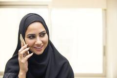 Mulher árabe nova bonita que fala no telefone celular Fotografia de Stock Royalty Free