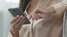 A mulher é assento furado na sala de visitas que enrola redes sociais e que lê a notícia video estoque