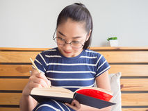 A mulher é livro de leitura na cama imagens de stock royalty free
