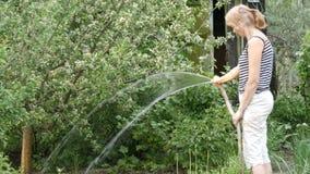 A mulher é plantas molhando em seu jardim de uma mangueira filme