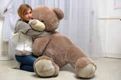 A mulher abraça um brinquedo grande Imagens de Stock Royalty Free