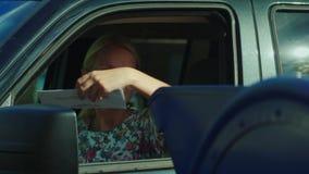 A mulher abre a janela de carro e joga a letra na caixa postal perto da estação de correios video estoque
