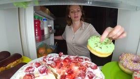 A mulher abre o refrigerador na noite Fome da noite glutonaria da dieta foto de stock