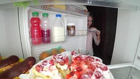 A mulher abre o refrigerador na noite Fome da noite glutonaria da dieta foto de stock royalty free