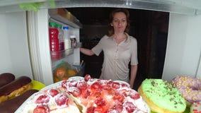 A mulher abre o refrigerador na noite Fome da noite glutonaria da dieta imagens de stock