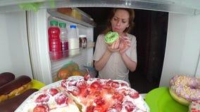 A mulher abre o refrigerador na noite Fome da noite glutonaria da dieta imagem de stock