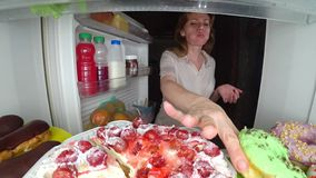 A mulher abre o refrigerador na noite Fome da noite glutonaria da dieta fotos de stock