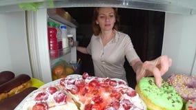 A mulher abre o refrigerador na noite Fome da noite glutonaria da dieta fotografia de stock royalty free