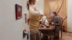 A mulher abre a porta do refrigerador e toma o leite na cozinha do conforto filme