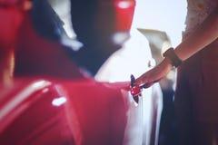 A mulher abre a porta a um carro novo, fim acima da mão da mulher que abre r imagens de stock royalty free