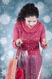 A mulher abre sacos de compras com fundo do inverno Foto de Stock