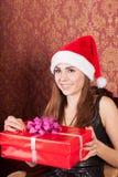 A mulher abre um presente do Natal Foto de Stock Royalty Free