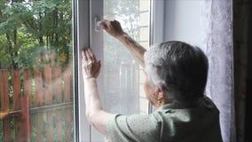 A mulher abre uma janela video estoque