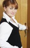 A mulher abre uma porta Fotos de Stock Royalty Free