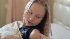 A mulher acorda e fala ao marido muscular adormecido na cama, alvorecer adiantado vídeos de arquivo