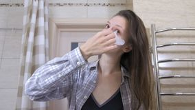A mulher acordada cansada remove os remendos dos olhos no banheiro vídeos de arquivo