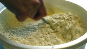 A mulher adiciona a farinha à massa e mistura-a Usa uma colher vídeos de arquivo