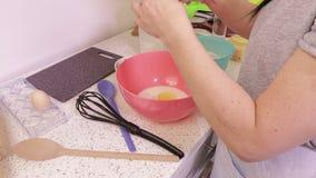 A mulher adiciona o leite e os ovos à massa video estoque