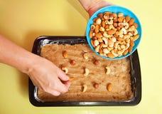 A mulher adiciona porcas na massa de pão Foto de Stock Royalty Free