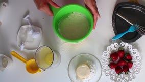 A mulher adiciona uma peneira e peneira a farinha para misturar a massa Ao lado da tabela são os ingredientes para a torta vídeos de arquivo