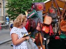 A mulher admira bolsas de couro bonitas Fotografia de Stock