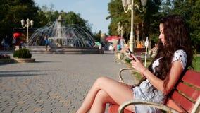 Mulher adolescente bonita de uma aparência caucasiano usando a tecnologia esperta app do telefone que senta-se em ruas de uma cid filme