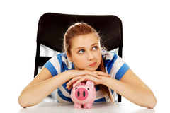 Mulher adolescente com piggybank na tabela Imagens de Stock