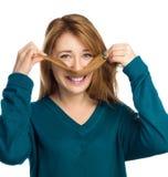 A mulher adolescente engraçada que põe o cabelo gosta do bigode Imagens de Stock