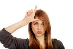 A mulher adolescente faz o sinal do vencido em sua testa imagens de stock royalty free