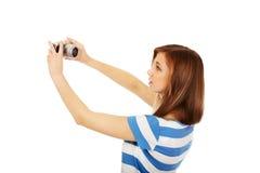 Mulher adolescente feliz que toma o selfie com a câmera clássica do slr foto de stock