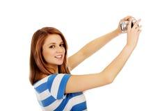 Mulher adolescente feliz que toma o selfie com a câmera clássica do slr foto de stock royalty free