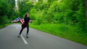 A mulher adolescente nova que acena uma bandeira dos E.U. é patinagem de rolo através das madeiras Movimento lento filme