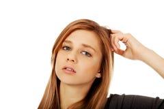 Mulher adolescente pensativa que risca sua cabeça Fotos de Stock Royalty Free