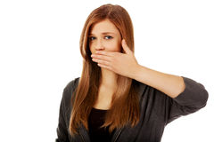 Mulher adolescente que cobre sua boca com a mão Fotografia de Stock Royalty Free