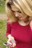 Mulher adolescente que emite sms Fotografia de Stock Royalty Free