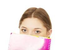 Mulher adolescente que esconde atrás de um caderno Imagens de Stock Royalty Free