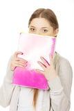 Mulher adolescente que esconde atrás de um caderno Fotos de Stock Royalty Free