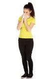 Mulher adolescente que espirra ao tecido Imagens de Stock