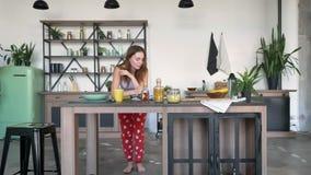 Mulher adorável do gengibre que lê o livro culinário e que dança na cozinha, estando com seus cotovelos na tabela, senhora redhea filme