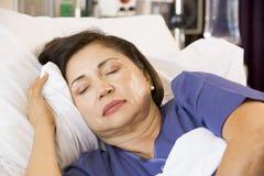 Mulher adormecida na cama de hospital imagem de stock