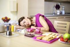 Mulher adormecida na tabela de cozinha durante o pequeno almoço Fotografia de Stock Royalty Free