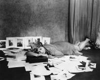 Mulher adormecida no assoalho cercado por ilustrações (todas as pessoas descritas não são umas vivas mais longo e nenhuma proprie Imagens de Stock