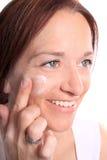 A mulher adulta aplica o creme na face Foto de Stock