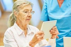 A mulher adulta aprende concentrado com a tabuleta fotos de stock royalty free