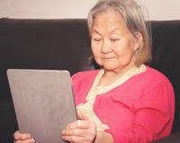 Mulher adulta assentada em um sofá usando uma tabuleta do écran sensível fotografia de stock