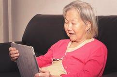 Mulher adulta assentada em um sofá usando uma tabuleta do écran sensível imagem de stock