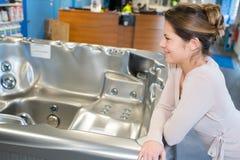 Mulher adulta atrativa que escolhe a mobília do banheiro na loja foto de stock royalty free