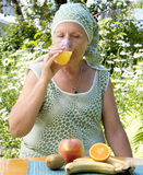 A mulher adulta bebe o sumo de laranja fresco Imagens de Stock