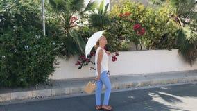 A mulher adulta bonita com guarda-chuva decorativo anda na rua vídeos de arquivo