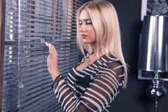 Mulher adulta com o cabelo louro que stanging perto da janela Imagens de Stock Royalty Free